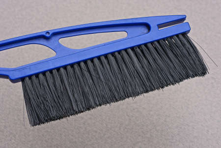 a big blue plastic brush sweeps dust off the gray wall