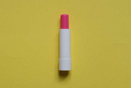 one white plastic bottle with red lipstick lies on a yellow table