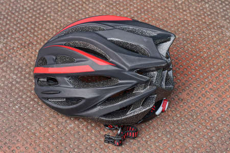 one big black plastic bicycle helmet with red stripes lying on a brown table