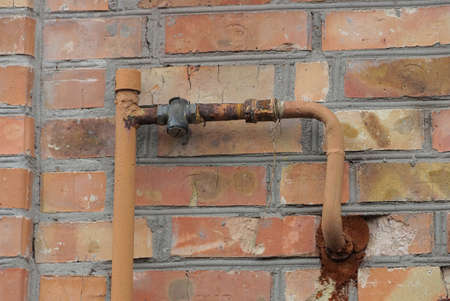 iron gas pipe on brown brick wall outside