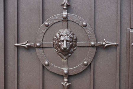 brown metal texture from wall with wrought iron pattern and lion head