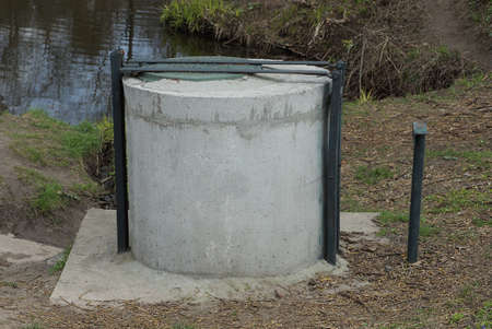 an old gray concrete well stands on the street on the shore of a reservoir