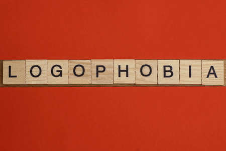text the word logophobia from gray wooden small letters with black font on an red table