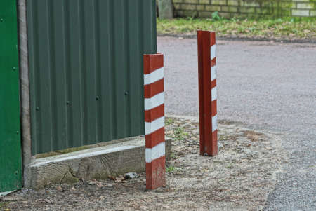 two striped iron fence posts by the road near the green metal wall of the fence on the street Standard-Bild