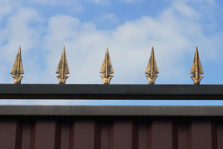 a row of yellow iron sharp rods on a black brown wall of a metal fence against a background of blue sky and white clouds