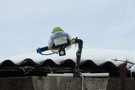 one led lamp on the roof of a house in white snow on a winter street