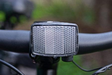 one white plastic reflector on a black metal sports bike handlebar outdoors