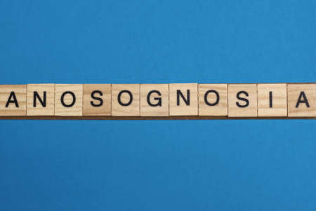 gray word anosognosia in small square wooden letters with black font on a blue background