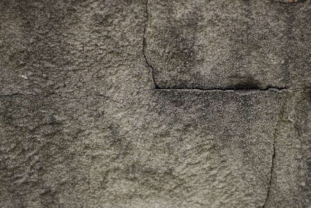 gray black stone texture with a black crack on dirty concrete wall