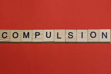 text the word compulsion from gray wooden small letters with black font on an red table