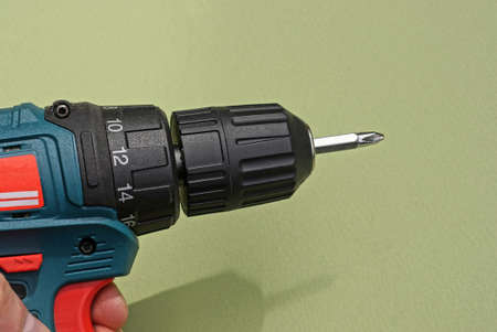 hand holds an electric black screwdriver on a green background