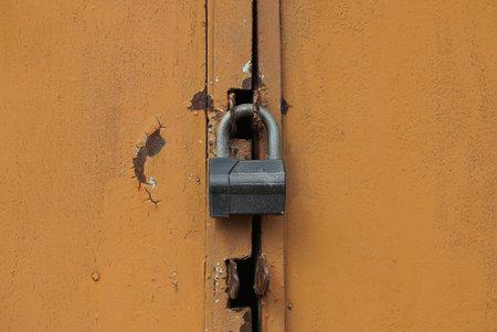 one gray big padlock on a brown iron door