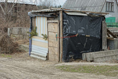 old gray wooden barn in black plastic cellophane on a rural street