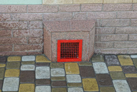 one red iron grate on the fan chimney on the brown wall by the sidewalk