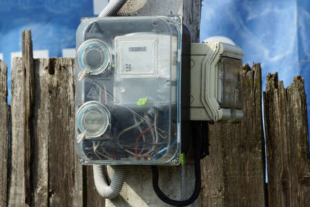 gray plastic electric and gas meters hang on a concrete post near a brown wooden fence wall outside