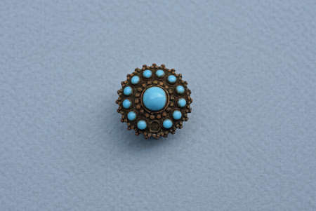 one small round old copper ornament with blue turquoise lies on a gray table
