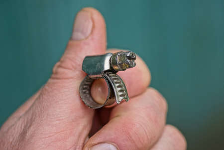 fingers hold one gray metal clamp with a bolt on a green background