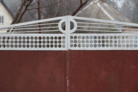 part of closed red white metal gate on a rural street Stockfoto