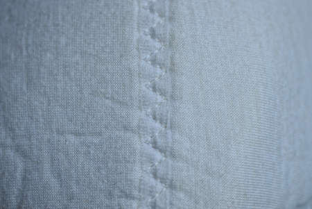 fabric texture of white seam with gray threads on woolen clothes