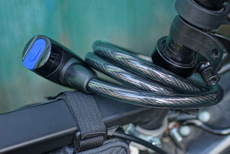 black bicycle lock with a cable screwed on the metal frame of a sports bike