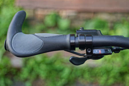 part of the bike from a black metal handlebar with a plastic gray handle and a brake with a cable on the green background