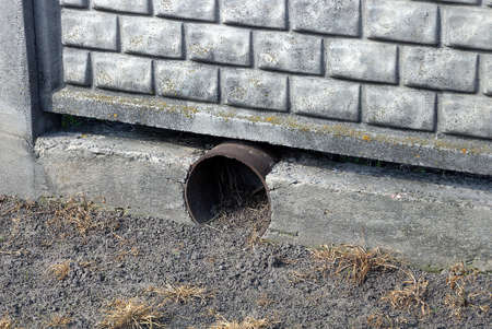 black metal gutter pipe in gray concrete fence wall on the ground outside