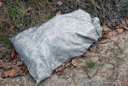 one large white plastic garbage bag lies on the gray ground outside