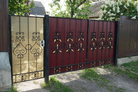 red metal gate and brown door with black wrought iron pattern on the street