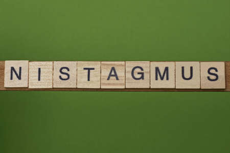 gray word nistagmus from small wooden letters on a green table