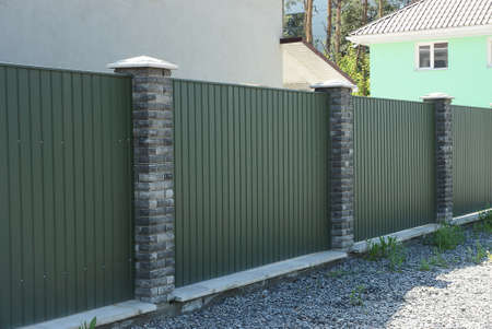 long fence wall of green metal and gray bricks on the street
