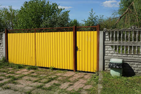 yellow metal gate with a closed door and part of a gray concrete fence outside in green grass