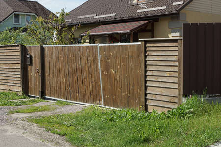 closed brown rural wooden gate and fence made of planks on the street on a green grass Stockfoto