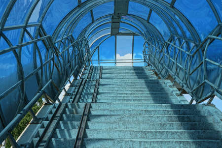 inside of a pedestrian crossing tunnel with gray concrete stair treads and blue plastic cover Stockfoto