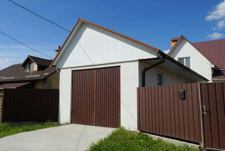 white garage facade with brown iron gate and part of a metal fence wall on the street Stockfoto