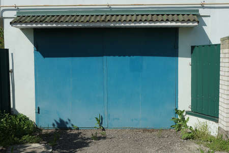 white facade of an old garage with blue metal gates outside in green grass Stockfoto