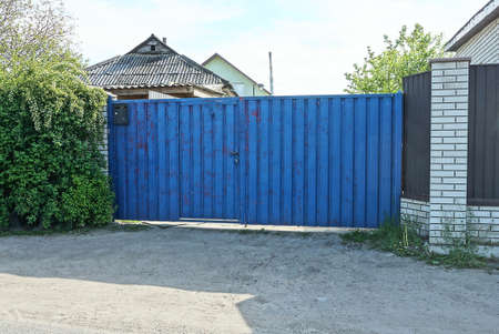 one big blue rural metal gate and part of the fence in the street Stockfoto
