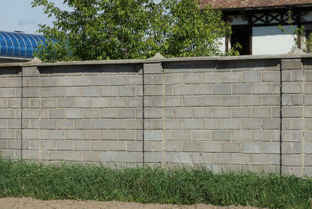 part of a large wall of a gray brick fence on a rural street in a green grass Stockfoto