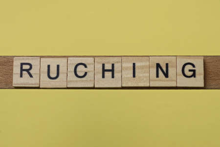 word ruching made from wooden letters lies on a yellow table