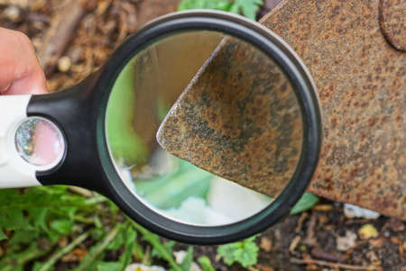 black magnifier in hand magnifies a rusty iron blade on an old hoe on the ground Stockfoto