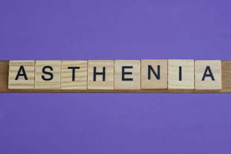 word asthenia in small square wooden letters with black font on a lilac background