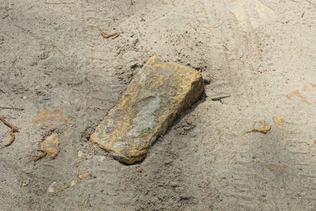one old brown brick lies on gray sand in the street