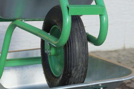 one black wheel on a green gray metal garden wheelbarrow on the street Stockfoto