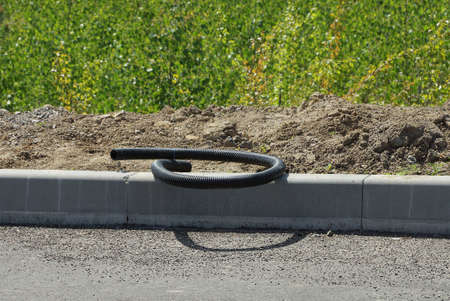 a black plastic hose lies on a gray concrete curb and on the ground outside against a background of green vegetation