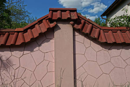 part of the pink stone wall of the fence under the red tiles in the street