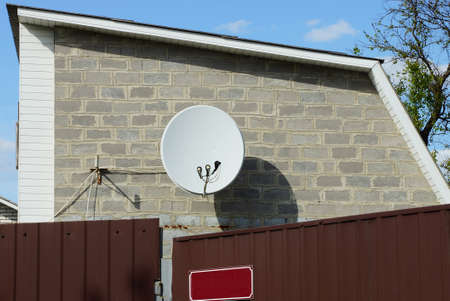 one white circular satellite dish hangs on a gray brick wall of a private house behind a metal brown fence against a blue sky