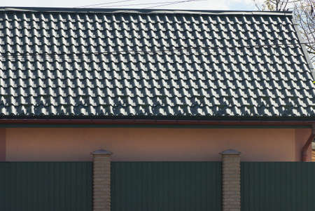 green tiled roof of a house behind a metal fence wall against a gray sky Stockfoto