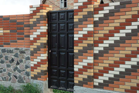 one black closed door on a colored brick wall of a fence outside