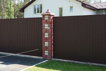 brown metal gate and part of the wall of the fence made of boards and red bricks on the street