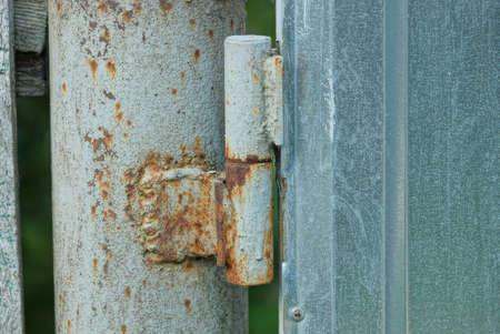 one old brown rusty iron door hinge on a gray metal wall