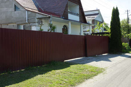 large closed red metal gate and wall fence on a rural street